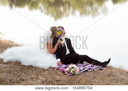 A bit of privacy. Bride and groom sitting on the grass kissing hiding their faces behind a colorful heart shaped candy