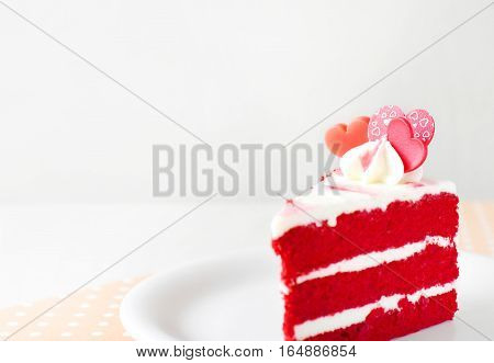 Close up shot of a piece of a strawberry layer cream cake with Valentines Day heart shaped decoration with white background copy space.