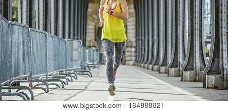 Outdoors fitness in Paris. Closeup on young sportswoman jogging on Pont de Bir-Hakeim bridge in Paris