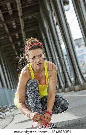 Woman Jogger Tying Shoelaces On Pont De Bir-hakeim Bridge, Paris