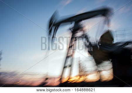 Work of oil pump jack on a oil field. Blurred motion.  Concept oil and gas industry.