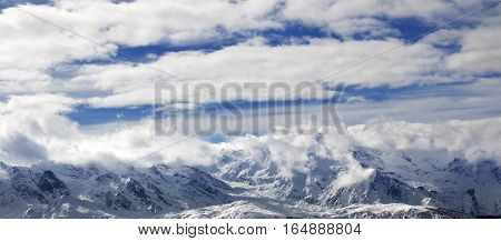 Panoramic View On Snow Mountains And Sunlight Cloudy Sky At Winter Evening
