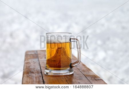 Glass mug with fresh cold beer on wooden bench in outdoor cafe at ski resort