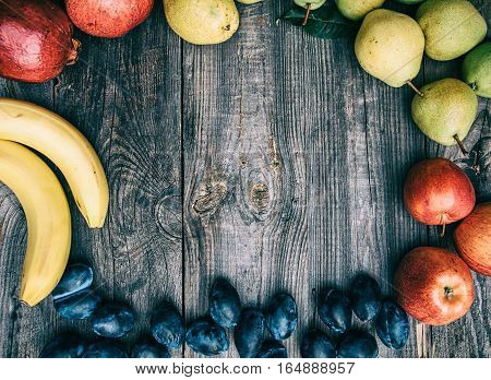 Fresh fruits are laid out on the perimeter empty space in the middle top view vintage toning