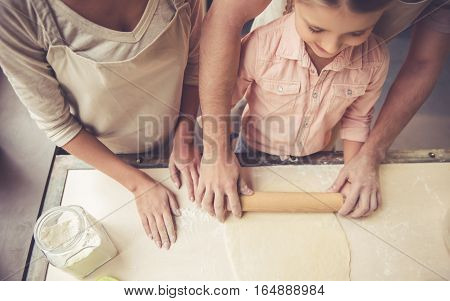 Top view of cute little girl and her beautiful parents flattening dough while baking in kitchen at home