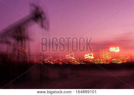 Work of oil pump jack on a oil field and brightly lit industrial site. Blurred motion.  Concept oil and gas industry.