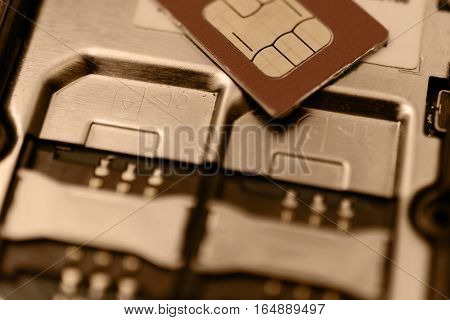 SIM card on slots in mobile phone. Close up view of the inside. Two seats for the card. Vintage toning.