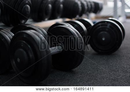 Rows of dumbbells at the gym. Dumbbells lie on the floor. Dark colors.