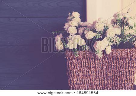 Beautiful flowers in wood bucket with pink rose on metal jug with vintage wood backround