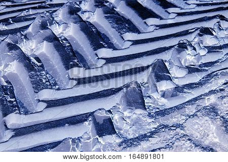 Off road tractor wheel tracks on road ice motoring background image. Industrial transport theme.