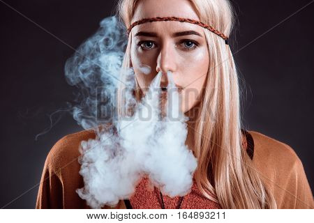 Young woman in the Boho style blowing smoke. The blonde on a dark background. Young woman looking into the camera. Close-up
