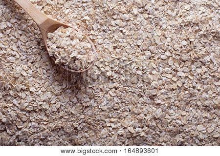 Oat flakes with wooden spoon. Oat texture