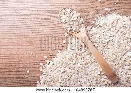 Oat flakes in the wooden spoon on the oat flakes background.