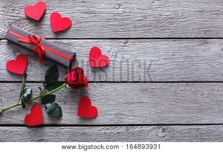 Valentine background with red rose flower, handmade paper hearts and small present box on rustic wood. Happy lovers day gift mockup, copy space