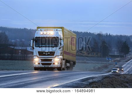 SALO FINLAND - JANUARY 1 2017: Stylish white MAN TGX 18.480 truck customized with lighting accessories hauls DHL trailer along highway on a blue winter evening.