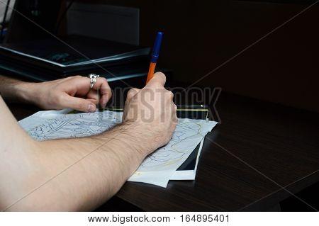 Artist encircles pen sketch of a tattoo on the desktop . The artist draws a sketch.