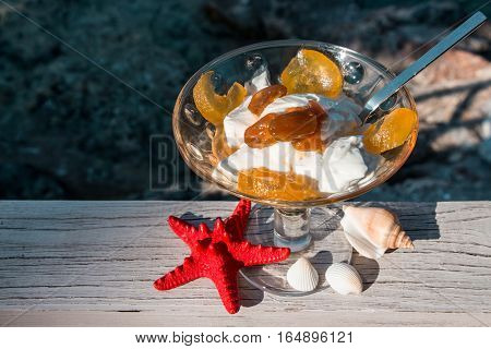 The bowl of greek yogurt with caramelized grapes for breakfast near seashells, red starfish on the sea background. Greek yogurt with caramelized grapes by the sea and seashells. Horizontal. Daylight.