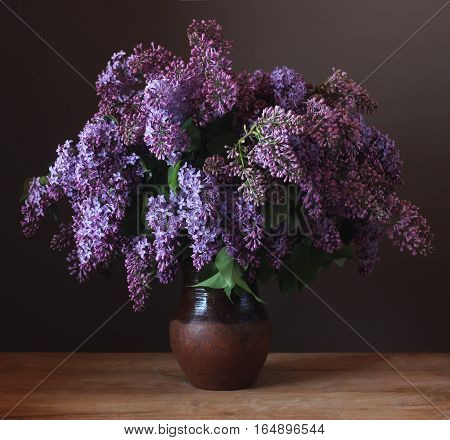 Bouquet of purple lilac in a clay jug on the table. Still life with flowers.