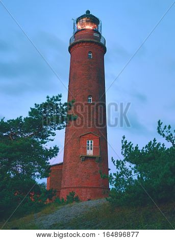 Old Lighthouse Above Dunes And Pine Tree  Before Sunset.