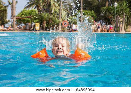 Girl having fun and  swimming in swimming pool