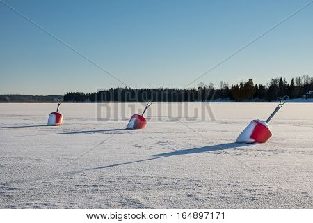 Three Large red buoys stuck in the ice on a clear freezing day in Sweden