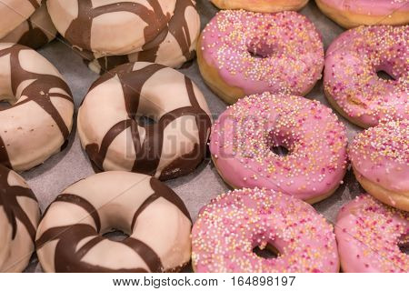 Closeup of fresh and newly baked pink and brown sugar coated donuts.