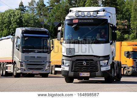SALO FINLAND - JULY 1 2016: White Renault Trucks T tractor and Volvo FH16 combination vehicle at a truck stop on a summer evening.