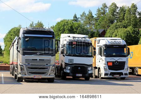 SALO FINLAND - JULY 1 2016: Modern Volvo FH Renault Trucks T and Mercedes-Benz Actros heavy goods vehicles parked at a truck stop yard on beautiful day of summer.