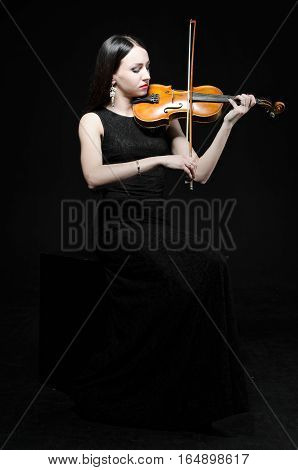 A young woman in a black dress with a violin on a black background.
