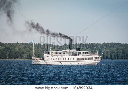 The white tour boat Mariefred a steam ship taking of for a guided tour with tourists. Steamboat Mariefred, Sweden, 2016-08-26