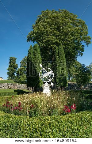 White sundial standing in the middle of a flowerbed.