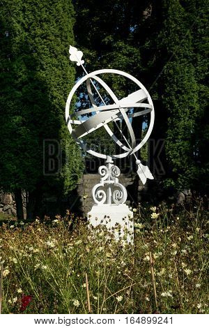 White sundial standing in the middle of a flower bed