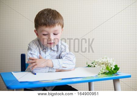 little boy sitting at a desk and listening to the teacher.