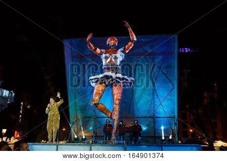 Barcelona Spain - January 02 2017: Tall dancing woman android is controlled by the group of people on the night stage of square of Catalunya during the Christmas holiday