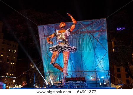Barcelona Spain - January 02 2017: Tall dancing woman android on the night stage of square of Catalunya during the Christmas holiday