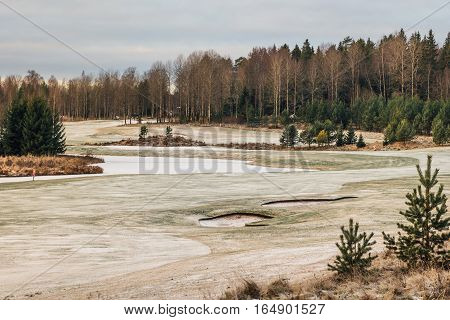 Golf course in winter closed and abandoned until next season. Ice and snow on the fairway.