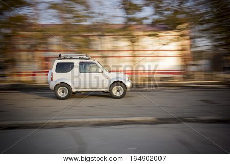 Russia - April 1, 2013: Car driving fast. White SUV at high speed driving on the road in the city
