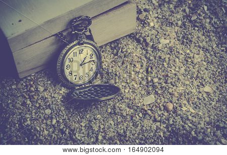 vintage pocket watch on sand beach with wood box