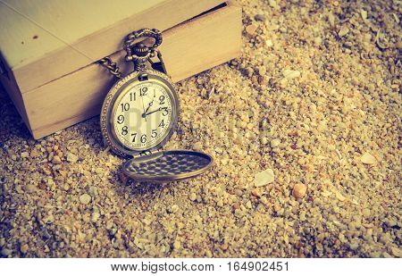 vintage pocket watch on sand beach with wooden box