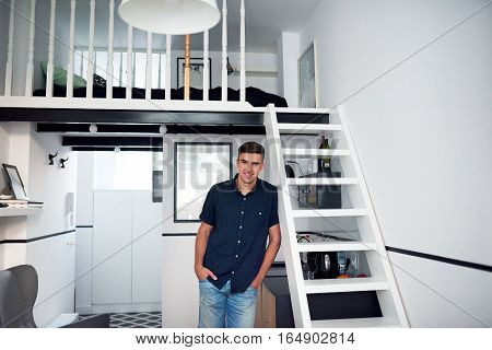 Portrait of a handsome young man smiling and leaning leaning on stairs while standing in his modern loft apartment