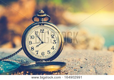 vintage pocket watch on blurred nature and sun light
