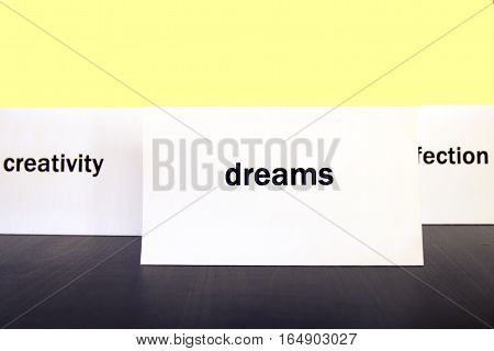 Word Dreams On A White Paper Card Surrounded By Other Words. Priorities And Values Concept