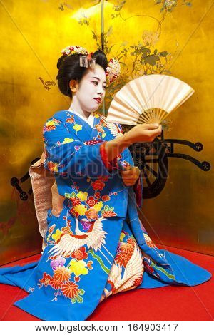 A photo of a dancing Geisha in kimono while holding a traditional fan in her hand.