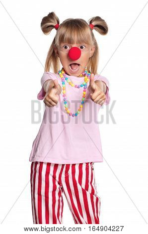 Little girl with clown nose showing thumbs up gesture, isolated on white background