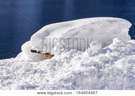 Snow Covered Picnic Table On The Mountain Lake. Winter Landscape.