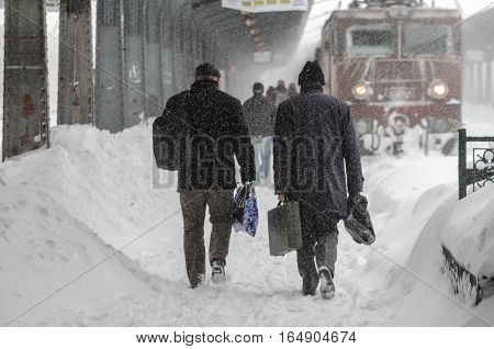 Bucharest Romania January 29 2014: People are going to the train in Gara de Nord main railway station during a blizzard.