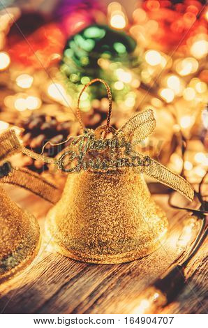 Christmas jingle golden bell decorations with rusty gold light bulb on wood background with copy space shallow depth of field