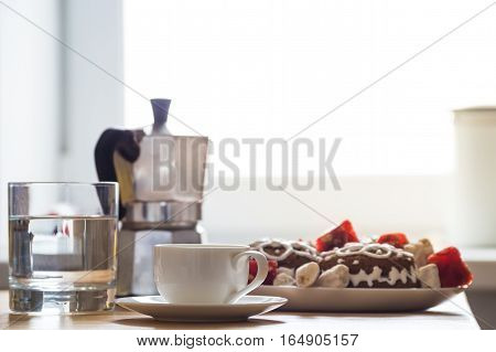 Holiday breakfast in home kitchen. Espresso cup, cookies and sweets, glass of water and italian moka coffee pot on natural wood table served for a christmas breakfast in front of window with sunlight