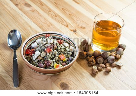 Christmas kutia and uzvar. Traditional ukrainian cereal wheat porridge with raisins nuts poppy seeds honey and candied fruit in earthenware bowl with dried fruit drink on natural wood table