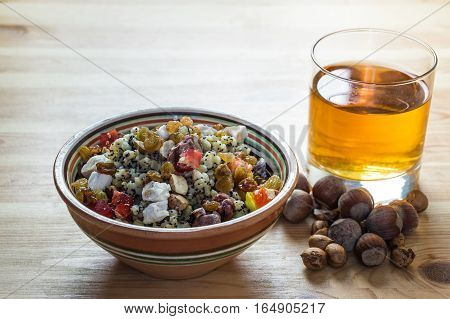 Ukrainian kutia and uzvar. Traditional christmas cereal wheat porridge with raisins, nuts, poppy seeds, honey and candied fruit in earthenware bowl with dried fruit drink on natural wood table